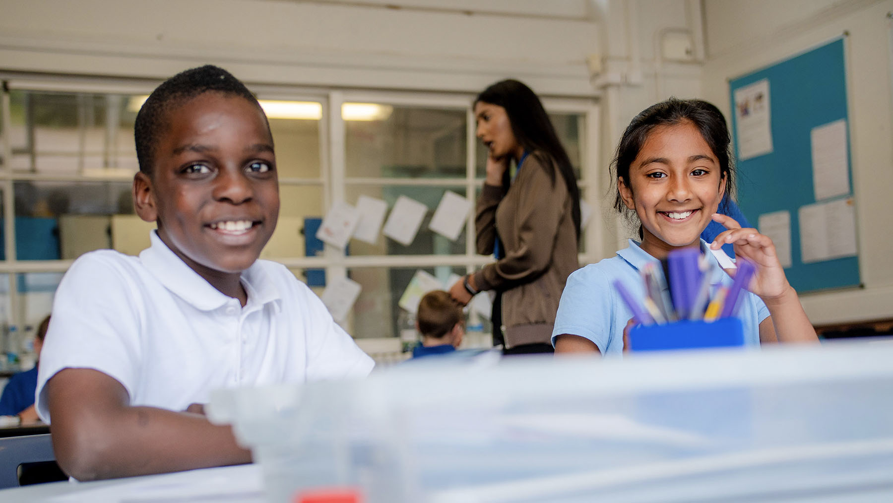 Boy and girl in classroom working at desk and smiling