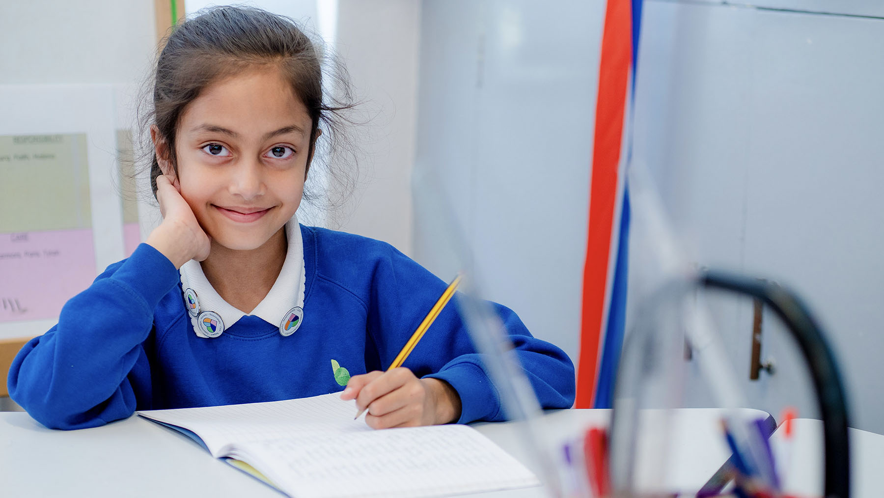 Girl working at desk in classroom smiling at the camera