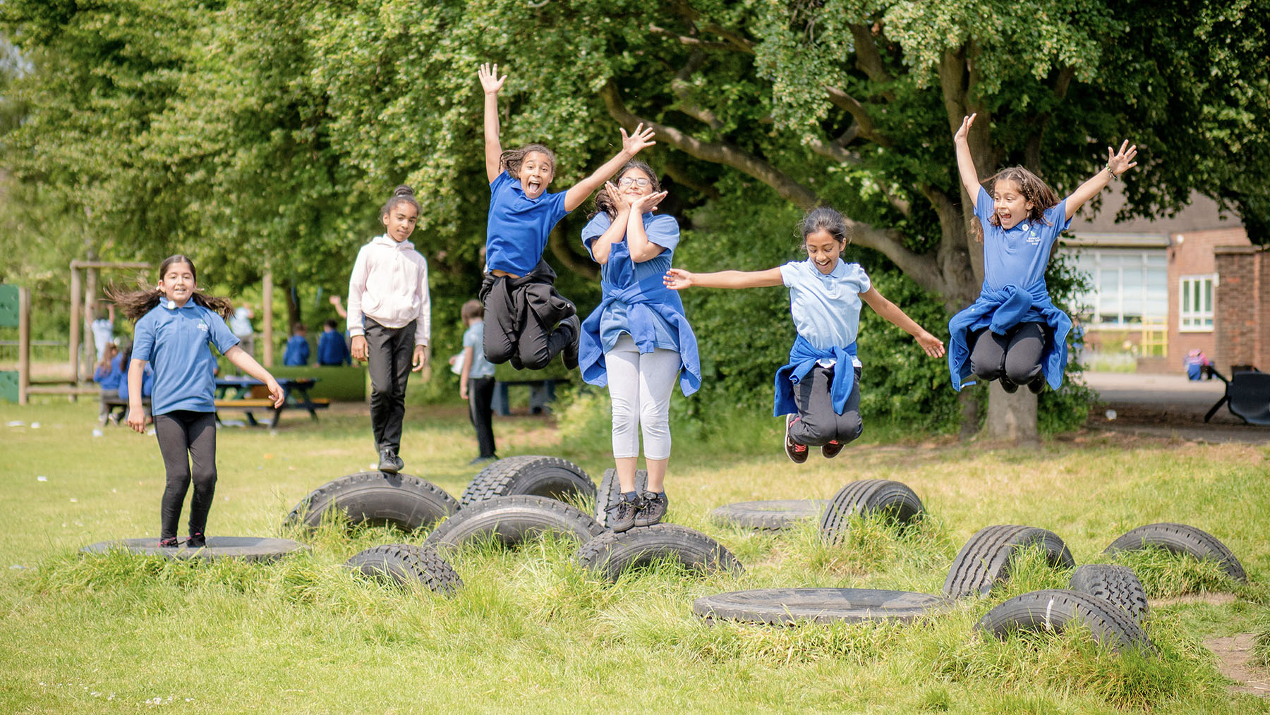 Girls jumping in the air from tyres on the playing field