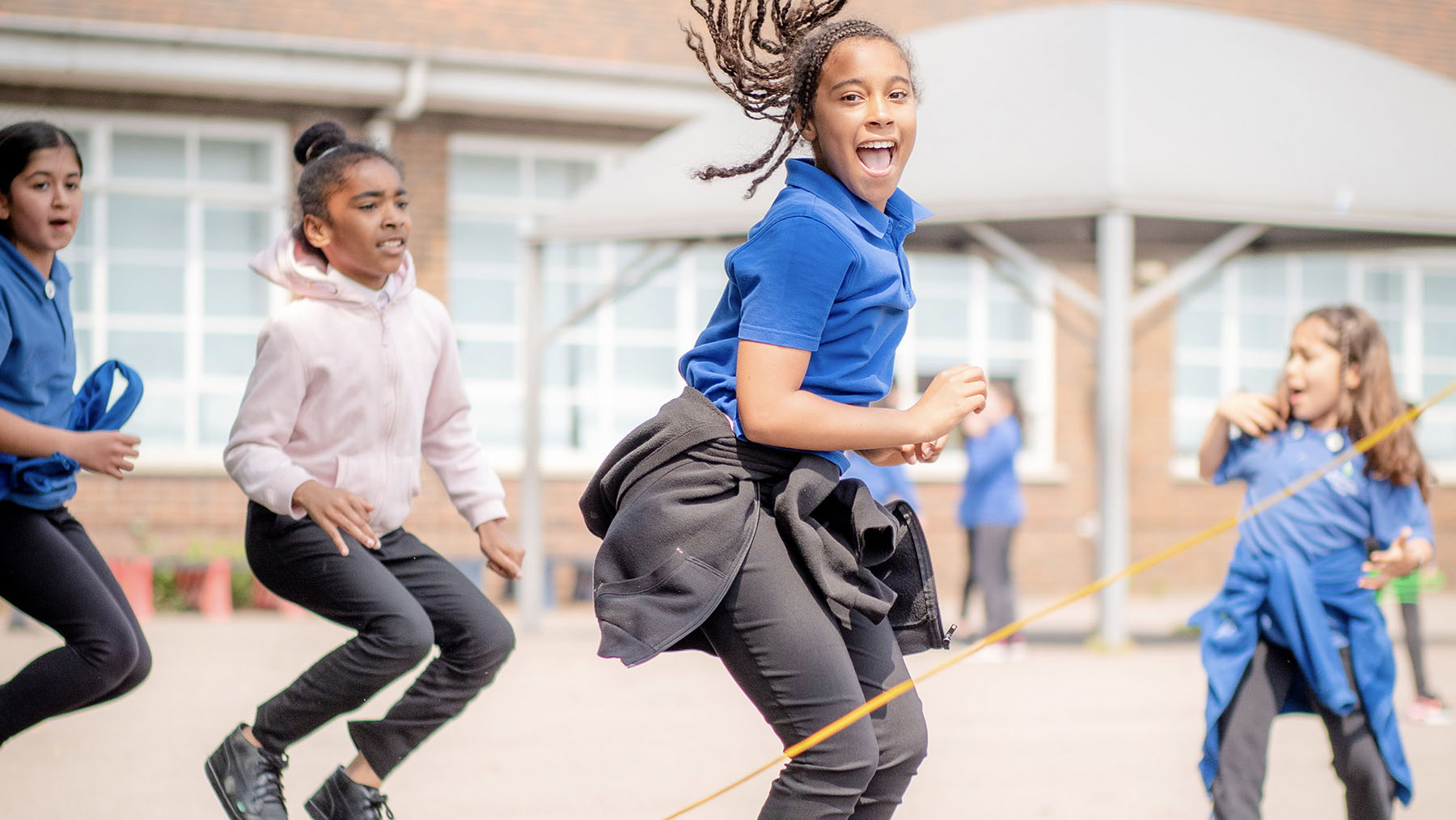 girls jumping on skipping rope in playground