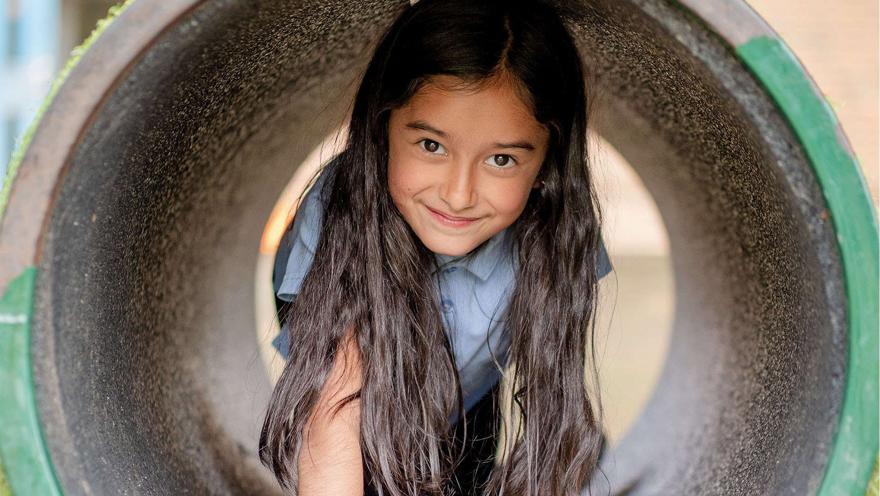 Girl in concrete tube in playground smiling