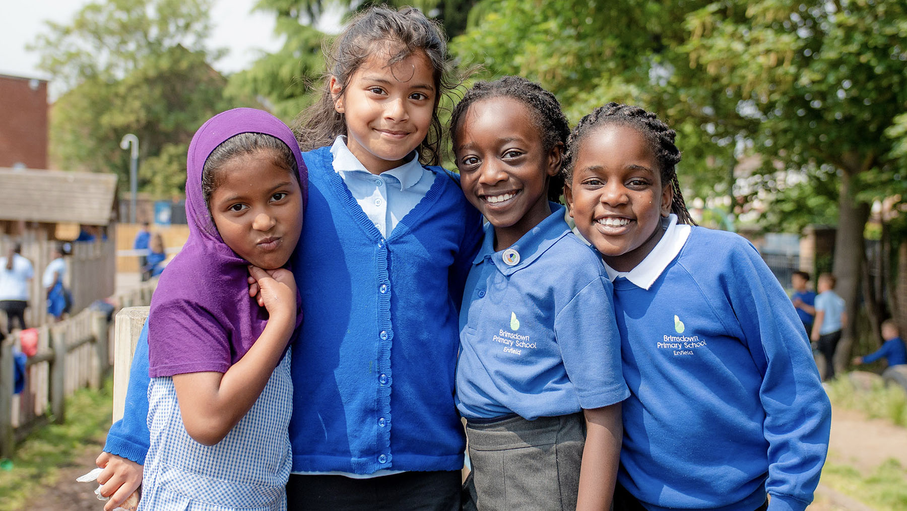 4 girls in the playground hugging and smiling