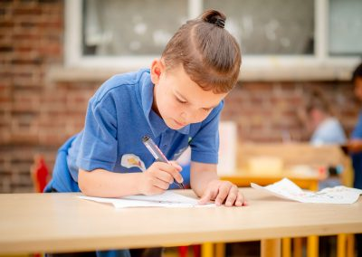 A young boy concentrating drawing on a table outside