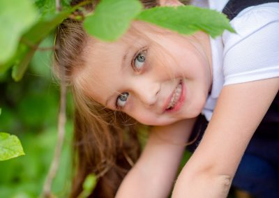 A close-up of a girl peering through some leaves