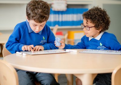 2 young boys working together at a table in the classroom