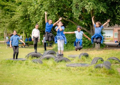 Some girls jumping off tyres in the school field