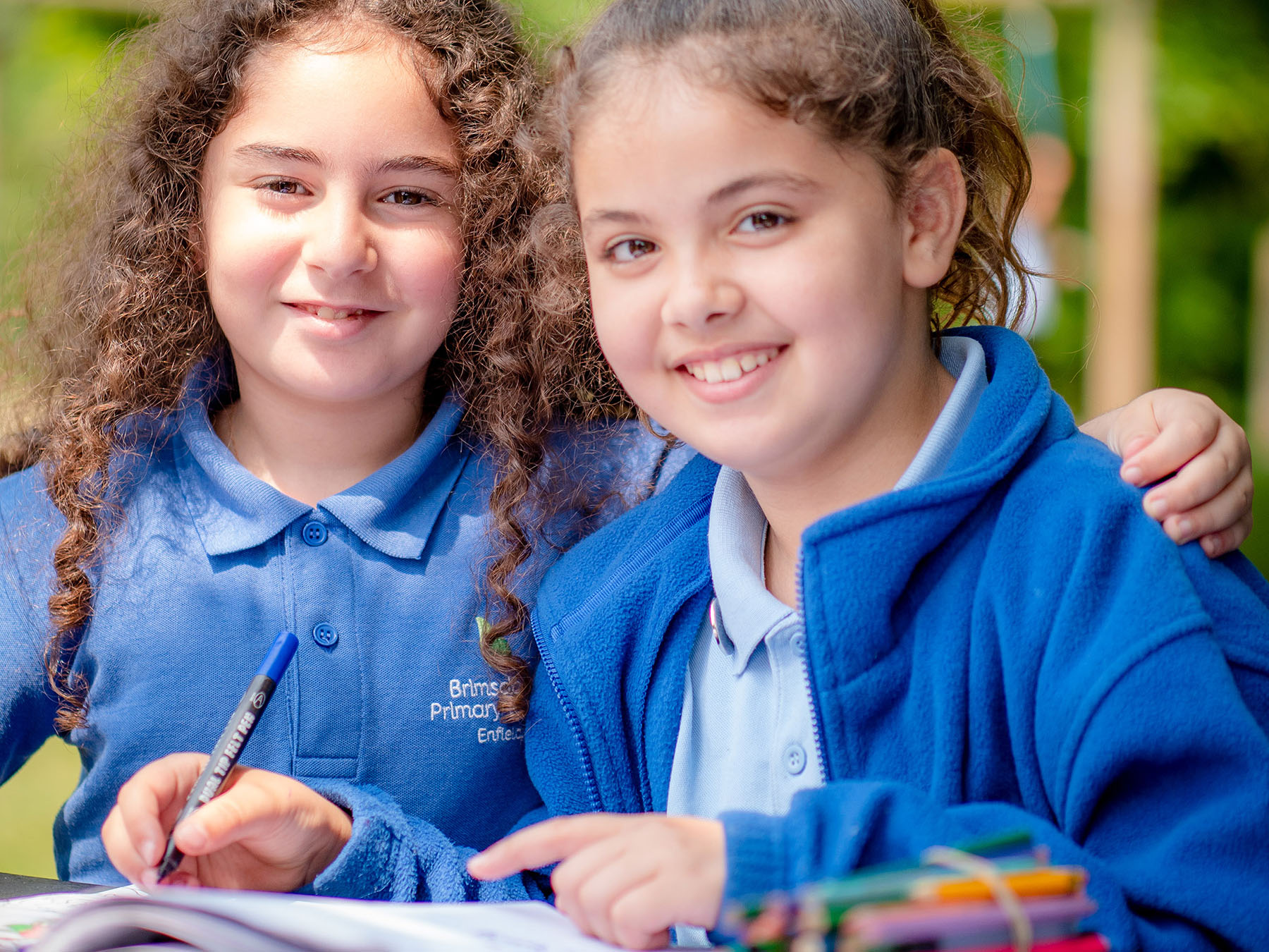 Two primary school girls working on bench outside smiling at the camera