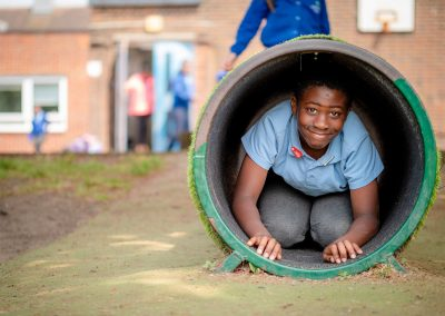 A boy smiling at the exit of a concrete tube in the playground