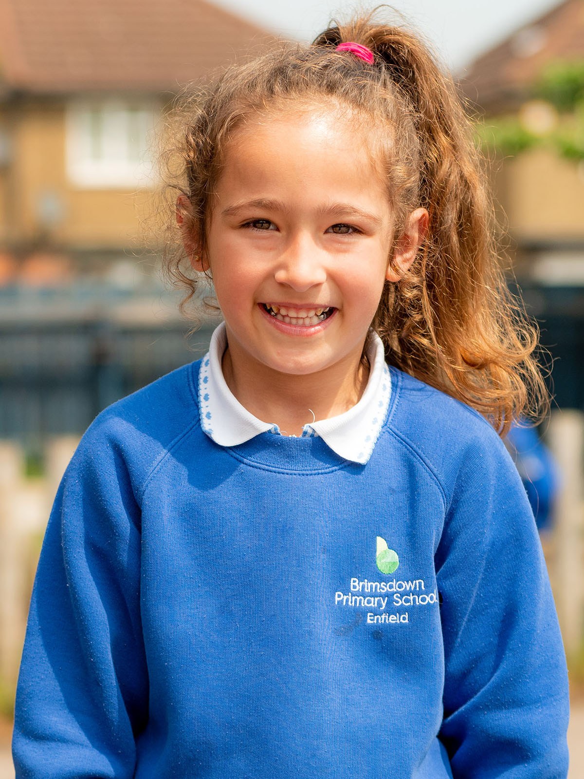 Upper body of young girl smiling in playground